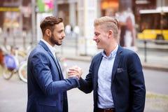 Två affärsmän som hälsar sig i gatan Arkivbild