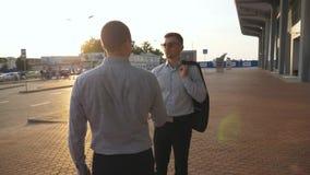 Två affärsmän som möter på stadsgatan och hälsar sig utomhus- affärshandskakning Skaka av manliga armar utanför arkivfilmer