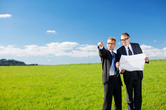 Två affärsmän som pekar på något arkivfoto