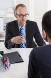 Två affärsmän som sitter i kontoret: möte eller jobbintervju arkivfoton