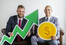 Två affärsmän som sitter på en soffa med finanssymboler Royaltyfri Fotografi