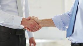 Två affärsmän som skakar deras händer stock video