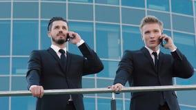 Två affärsmän som står nära trappräcket och talar på telefonen arkivfilmer