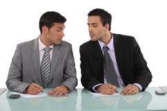 Två affärsmän som stjäler anmärkningar Arkivbild