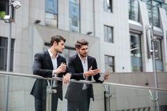 Två affärsmän som talar och använder minnestavlan i staden arkivbild