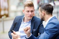 Två affärsmän som talar utanför i gatan royaltyfri bild