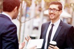 Två affärsmän som utomhus talar Arkivfoto