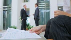Två affärsmän står i en korridor och diskuterar ungefärligt plan för arbete stock video