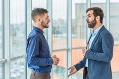 Två affärsmän talar om ett lyckat avtal Iklädd affärskläder arkivfoto