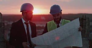 Två affärsman s som analyserar översikten av konstruktion, diskussion, bärande säkerhetsutrustning, fantastisk solnedgångbakgrund arkivfilmer