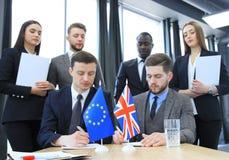 Två affärspartners som undertecknar ett dokument Den europeiska unionen och det stora britian Brexit Royaltyfria Bilder