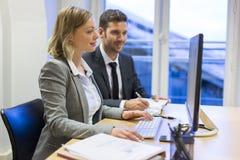Två affärspersoner i ett kontor som arbetar på datoren arkivbilder