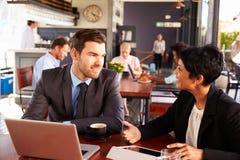 Två affärspersoner med bärbar datormöte i en coffee shop Arkivbild
