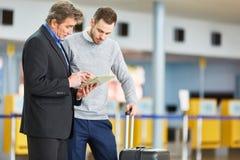 Två affärspersoner med minnestavlan i flygplatsterminal arkivfoton
