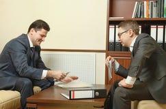 Två affärspersoner riktar förhandlingar i kontoret Arkivfoto