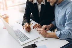 Två affärspersoner som arbetar på bärbar datordatoren med affärsdokumentet, grafdiagrammet och räknemaskinen på kontorstabellen royaltyfri foto