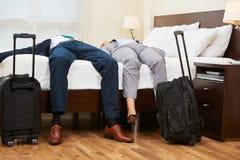 Två affärspersoner som lägger på säng i hotellrum arkivfoto