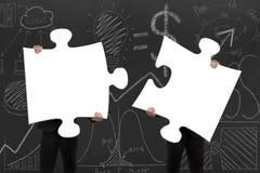 Två affärspersoner som monterar tomma vita pussel med D Fotografering för Bildbyråer