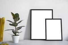 Två affischer i olika format i svart ram i den nordiska stilfulla moderna inre, fikus, vardagsrum Töm utrymme för designorienteri arkivfoto