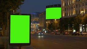 Två affischtavlor med en grön skärm I aftonen på en upptagen gata stock video