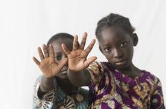 Två afrikanska barn som gör stoppet, undertecknar med deras händer som isoleras Fotografering för Bildbyråer