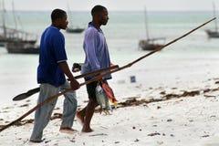 Två afrikanska fiskaredykare bär den hem fångade fisken Royaltyfria Foton