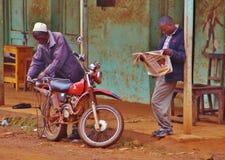 Två afrikanska män, en läsning Newpaperen och en Perparing hans Motorcyle fotografering för bildbyråer