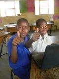 Två afrikanska skolbarn med bärbara datorn som visar tummar-upp arkivfoton