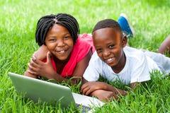 Två afrikanska ungar som lägger på gräs med bärbara datorn Arkivbild