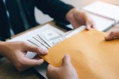 Två aktieägare har affärshemligheter med kassa som förläggas i dokumentkuvertet för att muta anställda arkivfoto