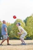 Två aktiva höga vänner som spelar fotboll Royaltyfri Fotografi