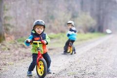 Två aktiva lilla siblingpojkar som har gyckel på cyklar i skog Royaltyfri Bild