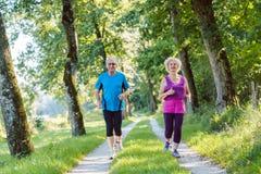Två aktiva pensionärer med en sund livsstil som ler, medan jogga tillsammans arkivbild