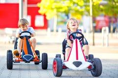 Två aktiva pojkar för liten unge som kör den pedal- racerbilen i sommarträdgård, utomhus Barn bästa vän som springer med snabbt arkivfoton