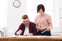 Två allvarliga arkitekter som diskuterar bygga plan Arkivfoton