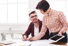 Två allvarliga arkitekter som diskuterar bygga plan Arkivfoto