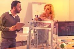 Två allvarliga coworkers som kombinerar deras kunskap för att få arbetet för skrivare 3D arkivfoto