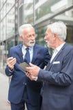 Två allvarliga höga affärsmän som arbetar på en minnestavla som ser de och diskuterar royaltyfri bild