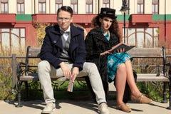 Två allvarliga personer som sitter på bänkläseboken Royaltyfria Foton