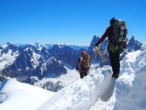 Två alpinister och bergsbestigareklättrare på Aiguille du Midi Arkivfoton