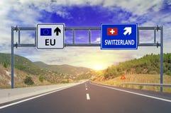 Två alternativ EU och Schweiz på vägmärken på huvudvägen Arkivbilder