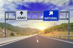 Två alternativ GMO och naturligt på vägmärken på huvudvägen Royaltyfria Foton