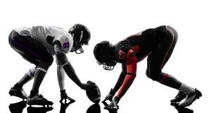 Två amerikanska fotbollsspelare på närkamp om bollenkontur Arkivfoto