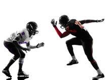 Två amerikanska fotbollsspelare på närkamp om bollenkontur Arkivfoton