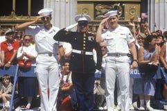Två amerikanska sjömän och Förenta staterna Marine Saluting på ståtar, Amerika Arkivfoto