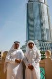 Två anonyma arabiska män i traditionella vita kläder som ser Arkivbild