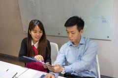 Två anställda känner sig roliga med information i rapport Royaltyfria Bilder