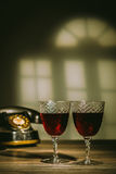 Två antika exponeringsglas som fylls med bordeaux Royaltyfri Fotografi