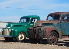 Två antika lastbilar-En återställdasom ut rostas Arkivbild