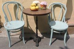 Två antika stolar och tabell utomhus Arkivbilder